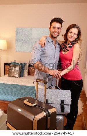 Loving couple embracing in hotel room upon arrival, smiling happy, looking at camera. - stock photo