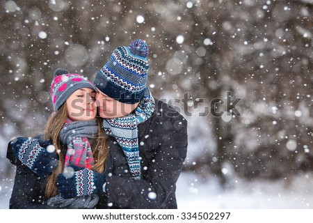 Loving couple embracing in winter park. They put colored caps and scarves. Loving warm hands to each other. Copy space. The girl hat with red hearts,  kissing. - stock photo