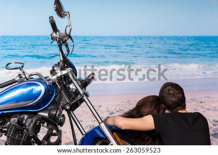 Loving couple enjoying a quiet day at the seaside sitting alongside their motorbike facing out over the ocean and waves on the golden sand - stock photo