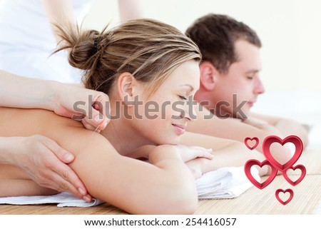 Loving couple having an acupunctre therapy against pink hearts - stock photo