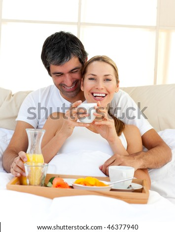 Loving couple having breakfast lying in the bed at home - stock photo