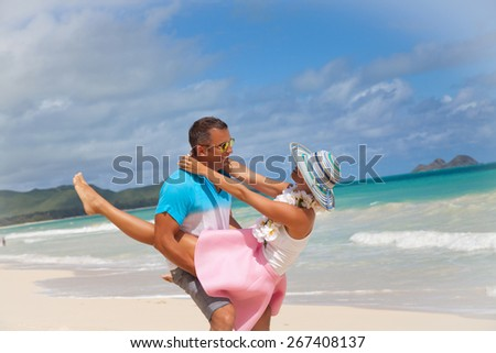 Loving couple having fun on the beach, enjoying their summer holiday together. Honeymooners on paradise beach with perfect pristine turquoise water in sunny tropical getaway, Oahu, Hawaii, USA.  - stock photo