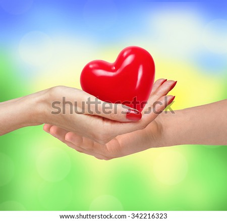 Loving couple holding heart in hands on sunny nature background - stock photo