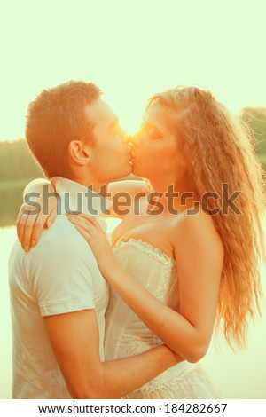 Loving couple hugging on the lake. Beautiful young woman and man in the background of the sun shining. Happy smiling Loves a date - stock photo