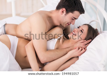 Loving couple in bed. Beautiful young loving couple lying in bed and looking at each other - stock photo