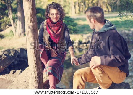 Loving couple in bright clothes meeting in the park near the lake - stock photo