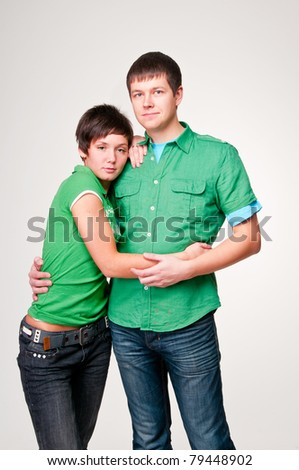 Loving couple in green shirts on a white background - stock photo