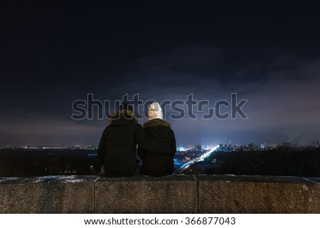 Loving couple looking at city night. Man and woman sitting in an embrace - stock photo
