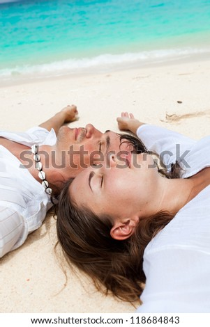 Loving couple lying on back on tropical beach, their faces closeup - stock photo