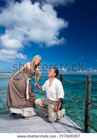 Loving couple on a wooden platform over the sea on the tropical island  - stock photo
