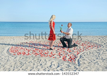 Loving couple on sea sandy beach - a man making proposal to his pretty blonde woman in red dress in the heart of roses petals - stock photo