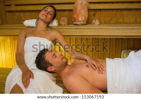 Loving couple relaxing in a sauna wearing white towels - stock photo