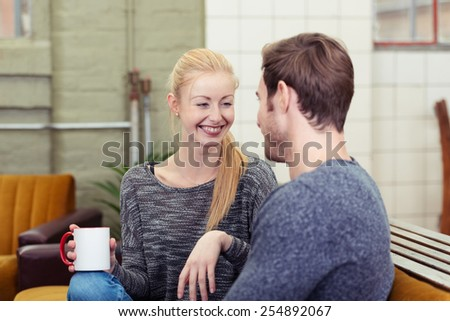 Loving couple relaxing over coffee in their living room sitting close together smiling happily into each other eyes, with focus to the woman over the husbands shoulder - stock photo