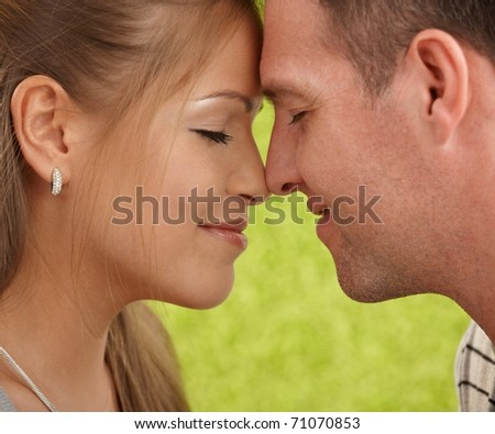 Loving couple's faces in closeup, foreheads touched, facing each other, smiling.? - stock photo