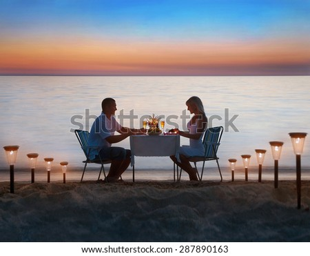 Loving couple share a romantic dinner with candles, lanterns and wine glasses at sea beach sand against wonderful sunset - stock photo