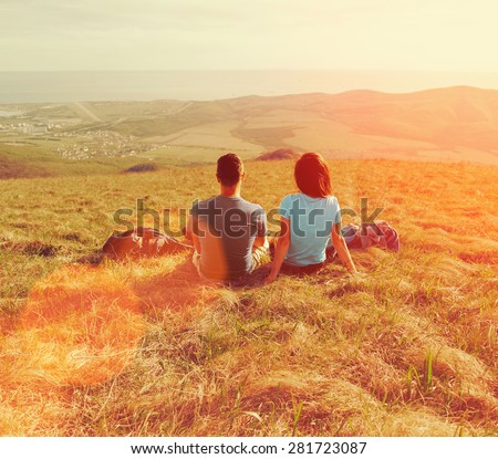 Loving couple sitting on mountain meadow and enjoying view of nature at sunny day in summer - stock photo
