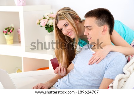 Loving couple sitting with laptop and credit card on sofa, on home interior background - stock photo