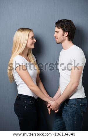 Loving couple standing holding hands facing one another smiling into each others eyes as they share a tender moment - stock photo