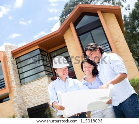 Loving couple talking to the architect about a house - stock photo