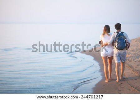 Loving couple walking along the seashore, view from the back - stock photo