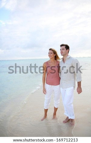 Loving couple walking by the beach at sunset - stock photo