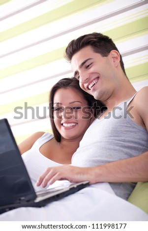 Loving couple with laptop and lying in bed - stock photo