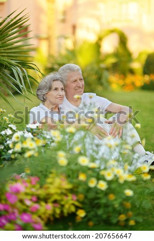 Loving elder couple sitting near flowers and palms - stock photo