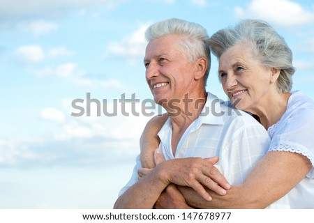 loving elderly couple on a background of clear sky - stock photo