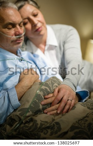 Loving elderly couple sleeping in bed sick husband - stock photo