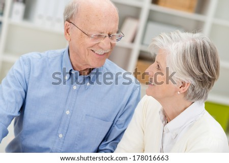 Loving elderly couple smiling at each other as they sit in an office having a discussion - stock photo
