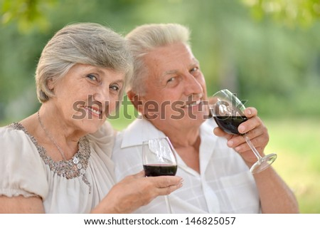 loving elderly couple spends time together in the summer outdoors - stock photo