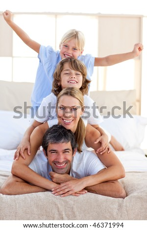 Loving family having fun in the bedroom - stock photo