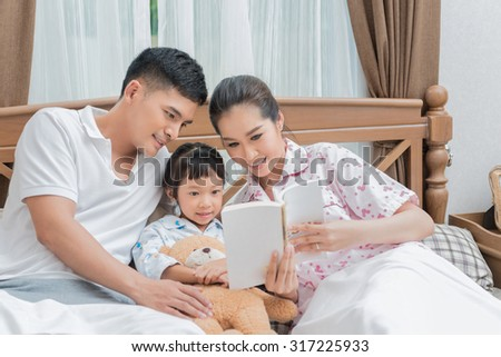 Loving family looking at a book on bed at home - stock photo