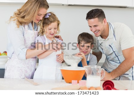 Loving family of four preparing cookies at kitchen counter - stock photo