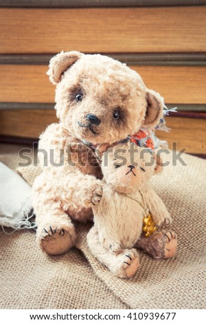 Loving family of two small vintage handmade textile sweet teddy bear art toys embracing together. Indoors closeup vertical close up image with retro filter. - stock photo