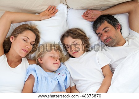 Loving family sleeping together lying in the bed - stock photo