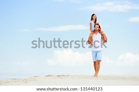 loving father with daughter on shoulders walking on the beach carefree and happy - stock photo