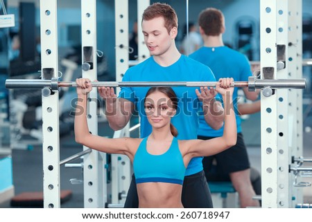 Loving fitness. Concentrated young beautiful woman in sports clothing doing exercises in the gym with a barbell while her sports instructor controlling the workout - stock photo