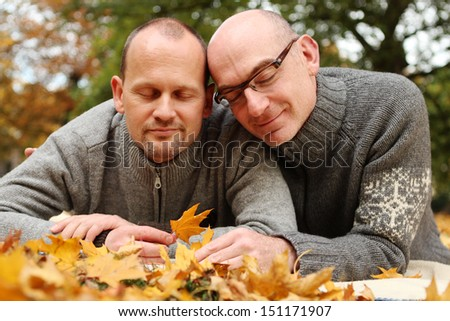 Loving gay couple with closed eyes Autumn Portrait - stock photo