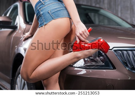 Loving good cars. Close-up of young woman touching her high heeled shoe while leaning at the car - stock photo