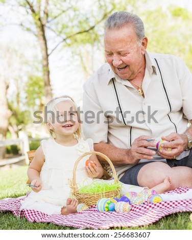 Loving Grandfather and Granddaughter Coloring Easter Eggs Together on Picnic Blanket At The Park. - stock photo