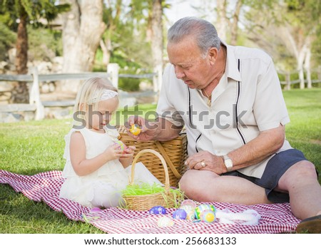 Loving Grandfather and Granddaughter Enjoying Easter Eggs on a Picnic Blanket At Park. - stock photo