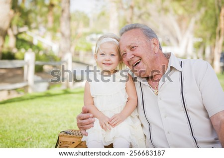 Loving Grandfather and Granddaughter Hugging Outside At The Park. - stock photo
