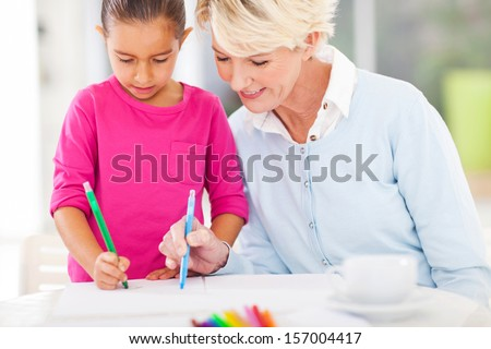 loving grandma teaching granddaughter drawing at home - stock photo