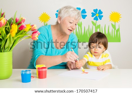 Loving grandma teaching her grandson to draw with paint at home - stock photo
