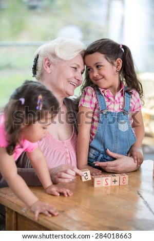 Loving grandmother teaching calculation to granddaughters at table in house - stock photo