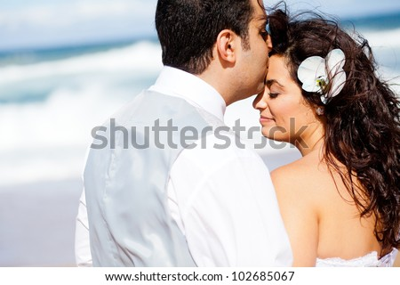 loving groom kissing bride's forehead on beach - stock photo