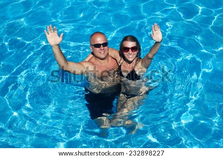 Loving happy couple in pool. Summer vacation. - stock photo