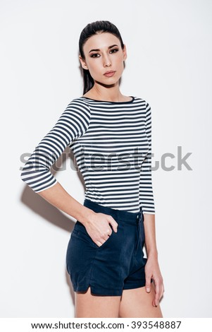 Loving her style. Beautiful young woman keeping hand in pocket and looking at camera while standing against white background - stock photo