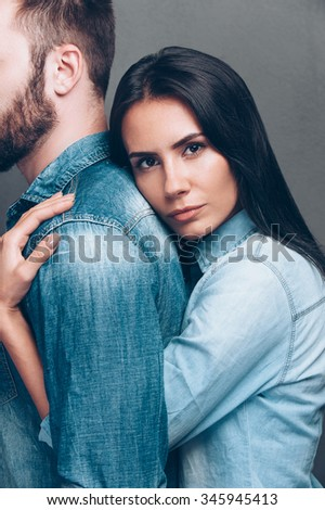 Loving him so much. Side view of beautiful young woman bonding to back of beard man and looking at camera while both standing against grey background  - stock photo